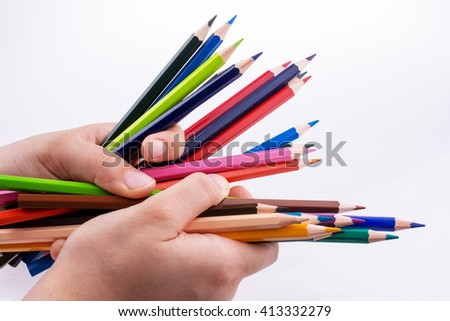 Hand holding color pencils on a white background - stock photo