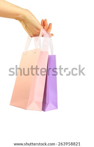 Hand holding colorful shopping bags isolated on white - stock photo