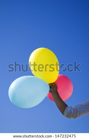 Hand holding coloured balloons