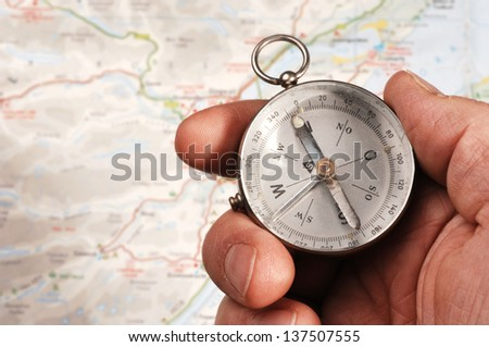 Hand holding compass, map (out of focus) in the background. NOTE: it���´s an old compass which contains some dust and dirt behind the glass - stock photo