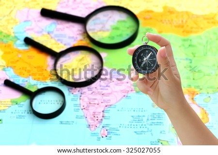 hand holding compass with blur black magnifying glass on map - stock photo