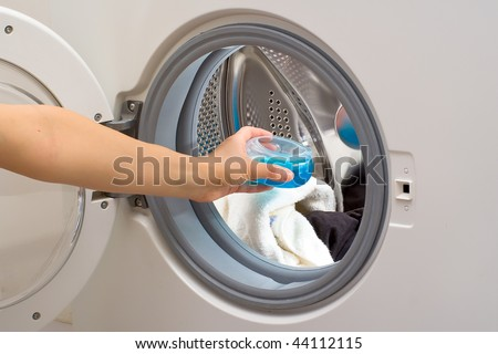 Hand holding container with washing gel in front of a drum of washing machine