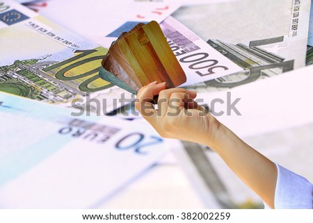 hand holding credit card with blur banknote background