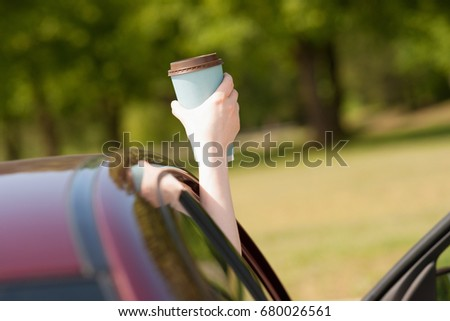 Hand holding cup of coffee in the car