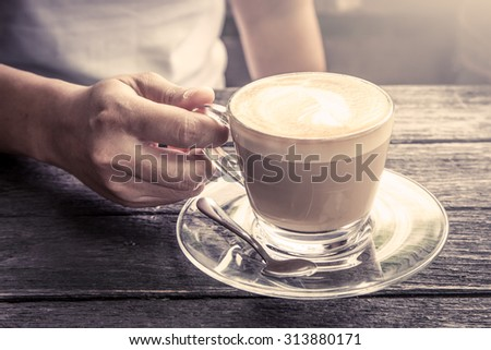 hand holding cup of coffee on wooden table in morning time in vintage color filter - stock photo