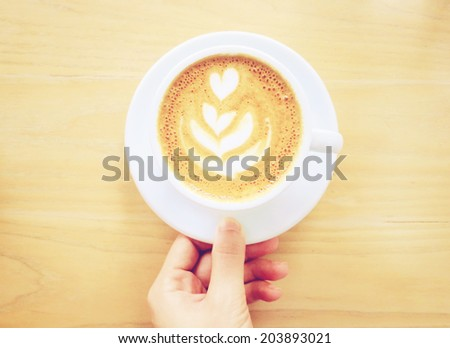 Hand holding cup of latte or cappuccino coffee with retro instagram filter effect                  - stock photo