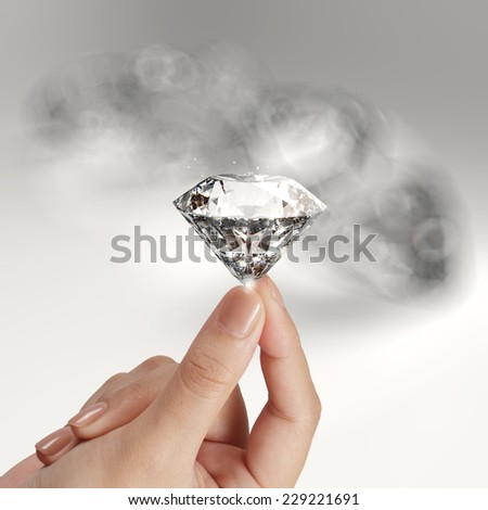 hand holding 3d diamond over grey background - stock photo