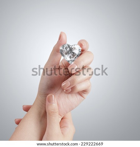 hand holding 3d heart shape of diamond over grey background - stock photo