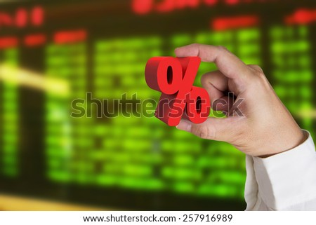 Hand holding 3D red percentage sign with display board background - stock photo