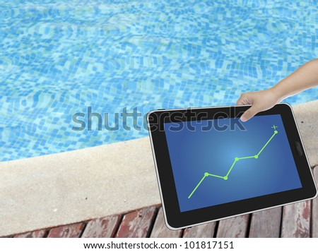 Hand holding digital tablet PC with a swimming pool background - stock photo