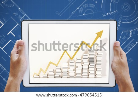 Hand holding digital tablet with raising up arrow graphs on screen, on architectural blueprint background