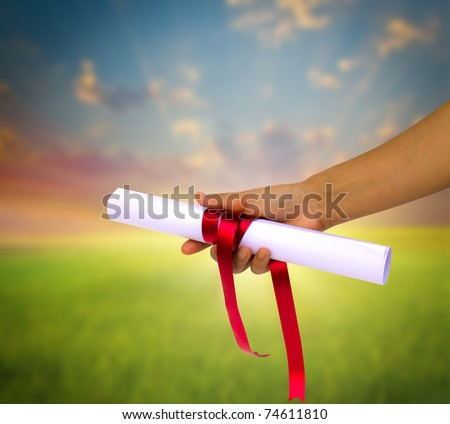 Hand holding Diploma wrapped with a red ribbon. - stock photo