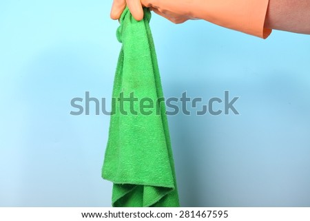 Hand holding dirty cleaning rag - stock photo