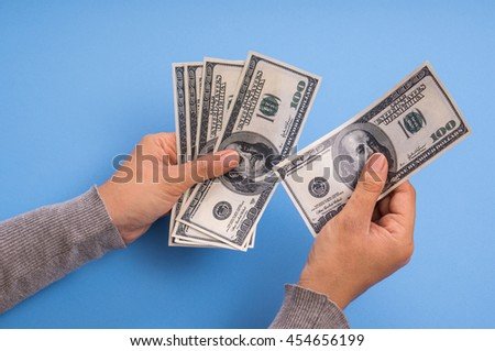 hand holding dollar banknote money and counting, blue background. - stock photo