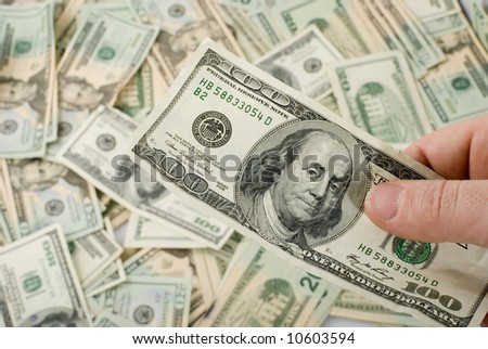hand holding 100 dollar bill over the heap of twenties - stock photo