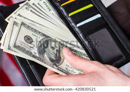Hand holding dollars and wallet. Wallet with cards and money. It was a busy month. Enough money for proper vacation. - stock photo