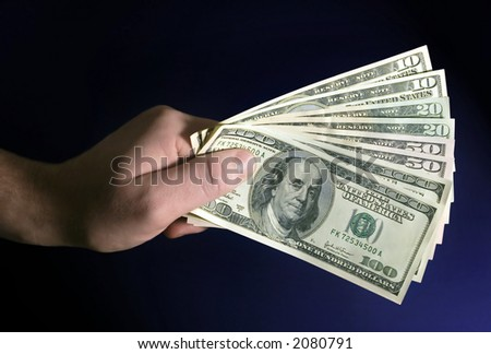 hand holding dollars in blue background. - stock photo