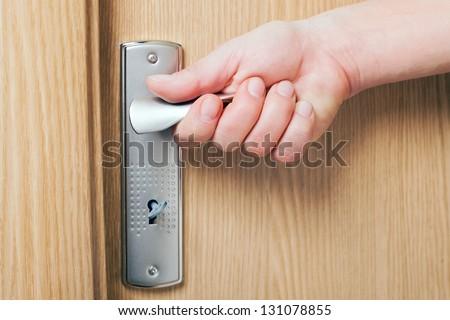 Hand holding door handle. - stock photo