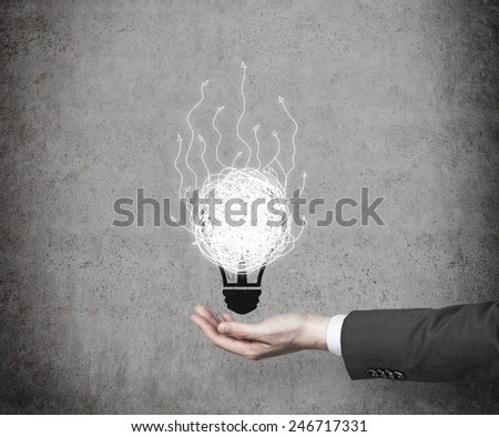 hand holding drawing bulb with arrows on blue background - stock photo