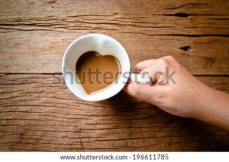 Hand Holding Drinking, Coffee Mug in Design of Heart Shape, Love and romantic idea on Wood Table Background, Rustic Style.