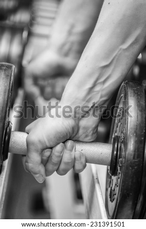Hand holding dumbbell.Close up.Muscular arm in the gym. Training, sports, hand, dumbbell, trainnings. - The concept of a healthy lifestyle and fitness. article about fitness and sports. - stock photo