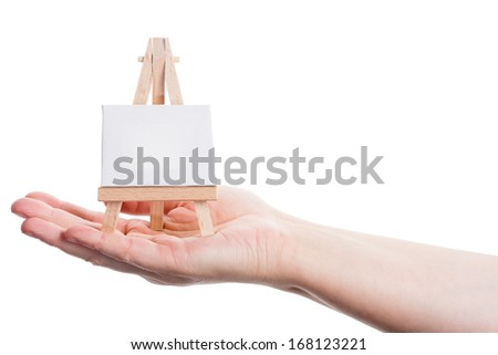 Hand holding easel with canvas isolated on a white background  - stock photo