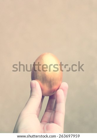 Hand holding easter egg with retro filter effect - stock photo