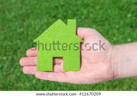 Hand holding eco house icon concept on the green grass background