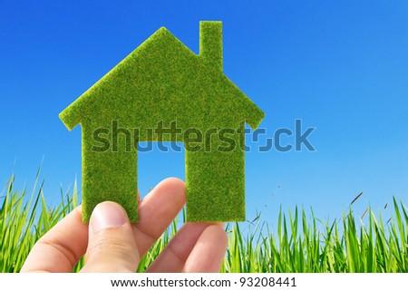 Hand holding eco house icon on nature background - stock photo