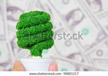 hand holding eco light bulb on dollars background ,save money concept