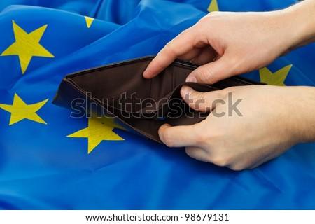Hand holding empty wallet, EU flag background - stock photo