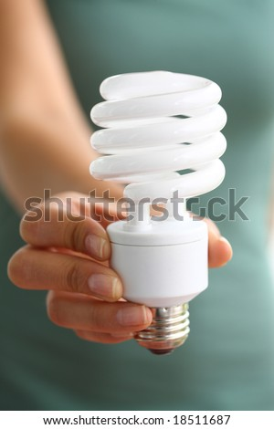 Hand holding energy efficient light bulb - stock photo