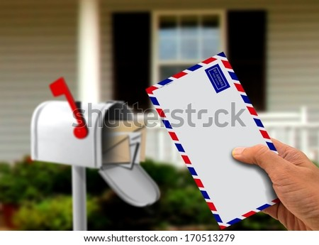 Hand Holding Envelope in Front of a House - stock photo