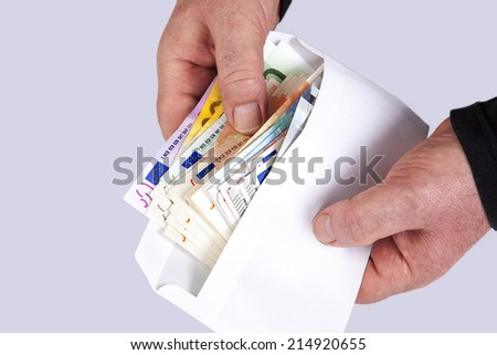 Hand holding envelope with paper money - stock photo