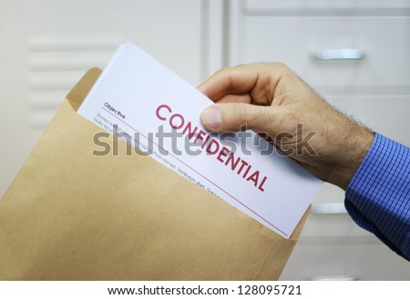 Hand holding envelope with top secret confidential documents - stock photo