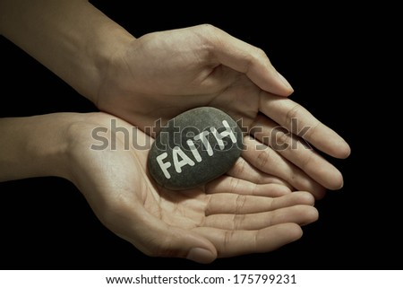 Hand holding faith word on stone - stock photo