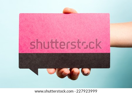 Hand holding female pink speech bubble on blue background. Woman concept. - stock photo