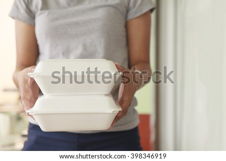 Hand holding foam boxes rice. - stock photo