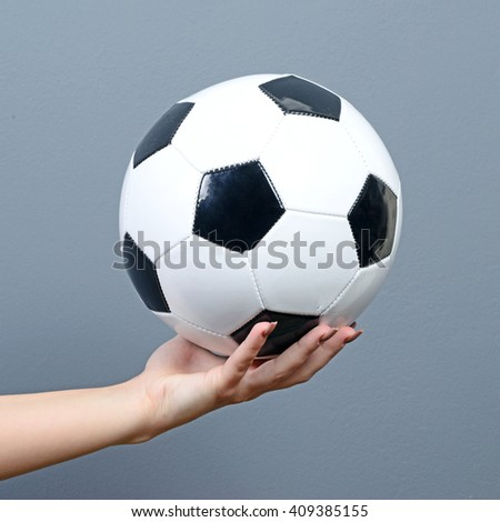 Hand holding football against gray background