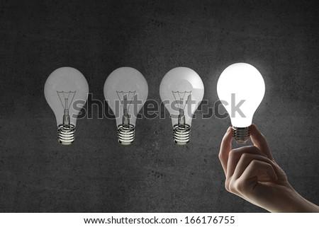 hand holding four light bulbs, idea concept - stock photo