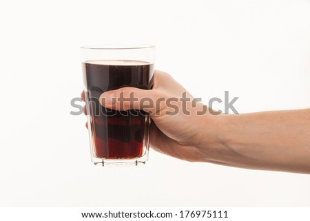Hand holding fresh cold glass of dark beer or kvass - stock photo
