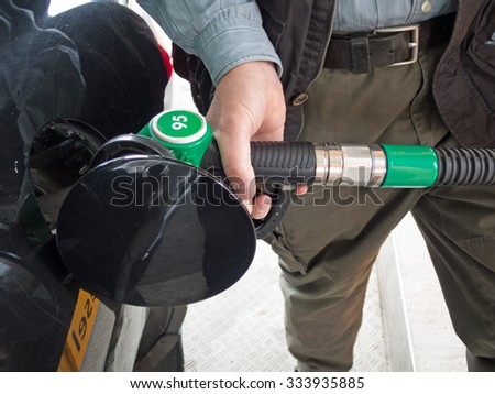 Hand holding fuel pump and refilling car  - stock photo
