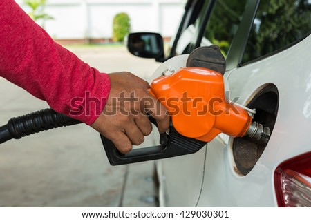 Hand holding fuel pump nozzle and refilling car.