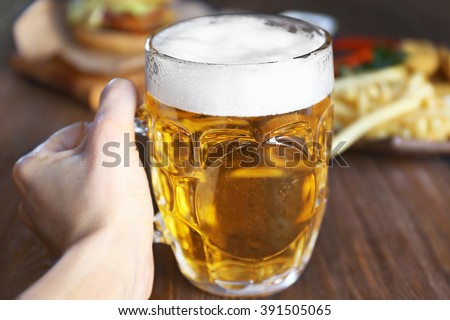 Hand holding glass mug of light beer with snacks on dark wooden table, close up - stock photo