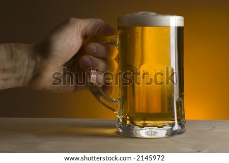 hand holding glass of beer on orange background - stock photo