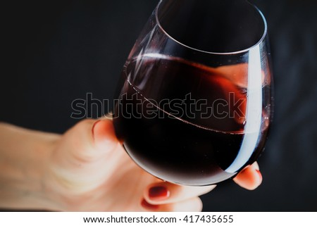 Hand holding glass of red wine on dark grey background