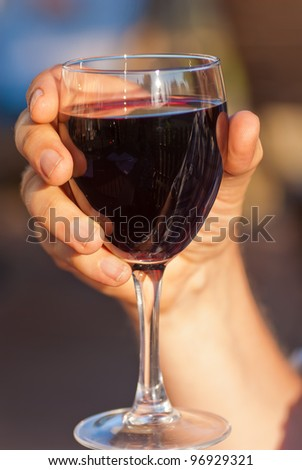 Hand holding glass of red wine outdoors in evening. - stock photo