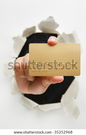 Hand holding gold credit card through cracked wall means breakthrough in credit card innovation - one of the breakthrough series - stock photo