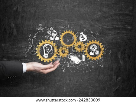 hand holding gold gears with business icons - stock photo