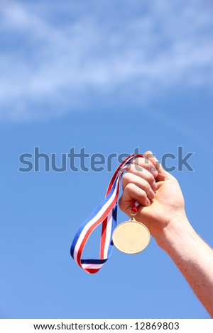 Hand holding gold medal - stock photo